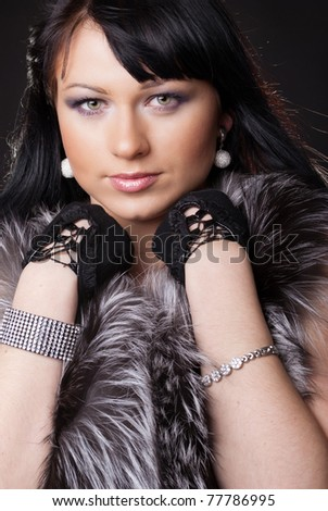 Woman in fur coat on black backgound - stock photo