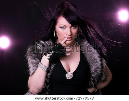 Woman in fur coat on black backgound and magenta light - stock photo