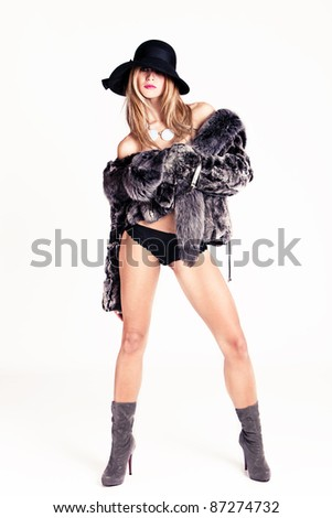 woman in fur, hat and winter boots, studio shot