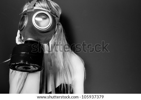 Woman in gasmask against wall