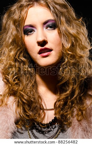 woman in glam rock style on black background