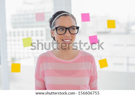 Woman in glasses in creative office looking away - stock photo