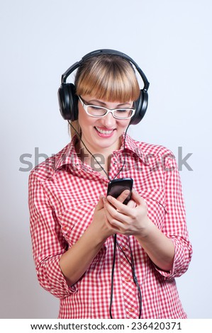 woman in glasses listens to music in earphones by means of the smartphone - stock photo