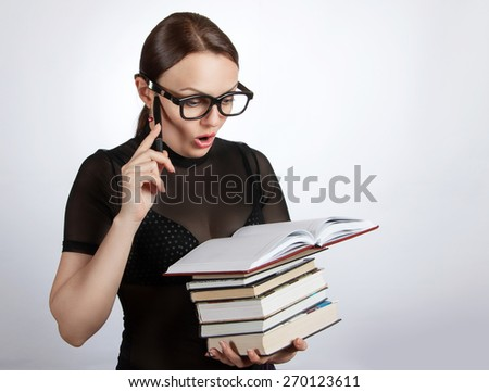 Woman in glasses with a stack of books. Portrait of a surprised woman