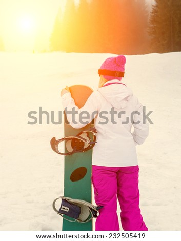 Woman in glasses with snowboard - stock photo