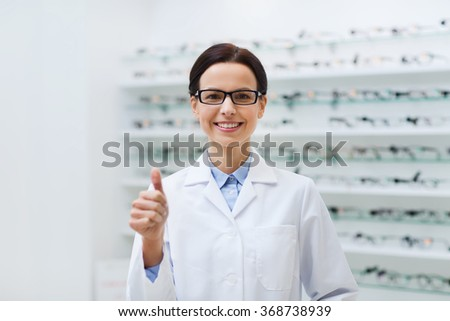woman in glasses with thumbs up at optics store - stock photo