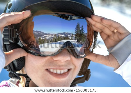 Woman in goggles and helmet stay on the snow - stock photo