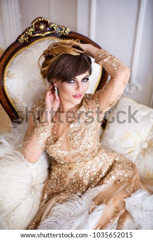Woman in gold dress, straightens hair. Sits on the couch