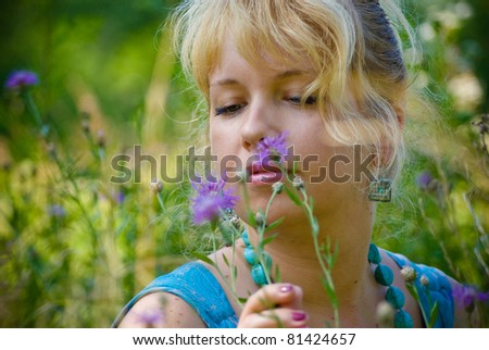 woman in grass with violet flowers