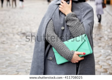 Woman in gray coat with light green handbag in hands walking down the rainy city streets. Street fashion look.  - stock photo