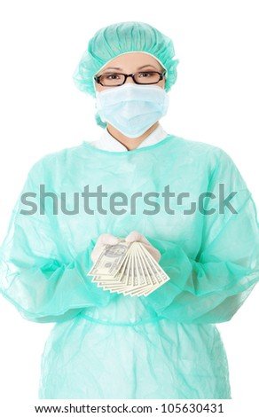 Woman in green medical uniform is standing and holding dollar bills. Isolated on the white background. - stock photo