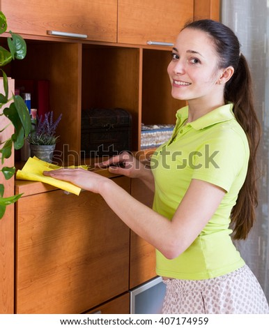 Woman in green wiping the dust from wooden furniture at the home  - stock photo