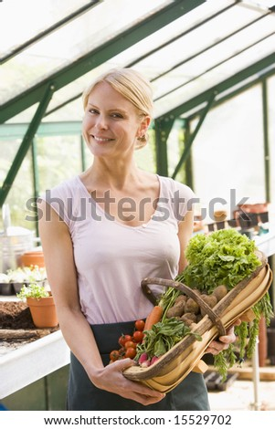 Woman in greenhouse holding basket of vegetables smiling - stock photo