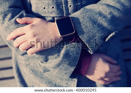 Woman in grey coat wearing stylish smart wrist watch. This person is always connected to social media and internet. Modern technology and vintage hipster film toning