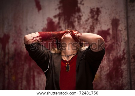 Woman in grief with bloodstained hands on the bloody wall background