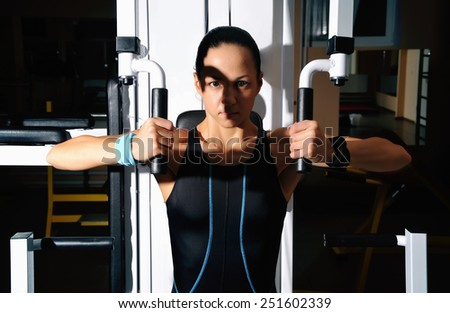 Woman in gym. Beautiful muscular fit woman exercising building muscles - stock photo