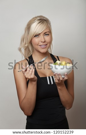woman in gym clothes eating a bowl of nice fruit - stock photo