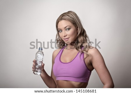 Woman in gym clothes holding bottled water - stock photo