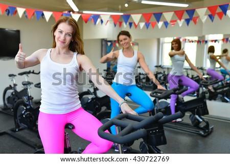 Woman in gym doing cardio on exercise bikes - stock photo