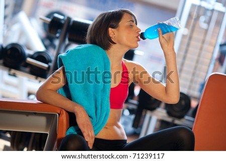 woman in gym drinks energy drink from bottle - stock photo
