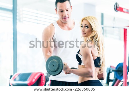 Woman in gym training for body building competition with barbell assisted by personal fitness trainer - stock photo