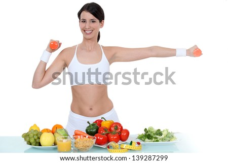Woman in gym-wear stood with vegetables - stock photo