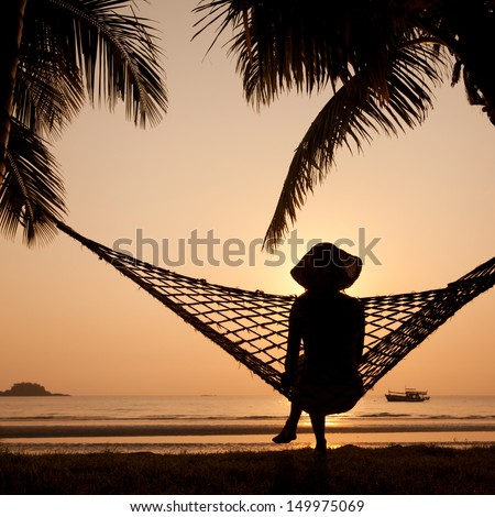 woman in hammock enjoying sunset on the beach - stock photo