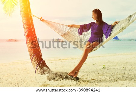 Woman in hammock on tropical beach