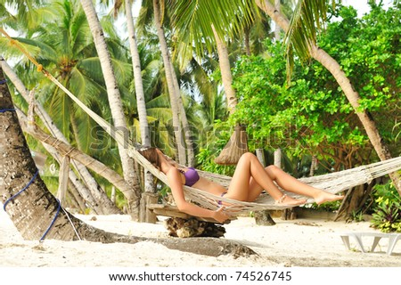 Woman in hammock on tropical beach - stock photo