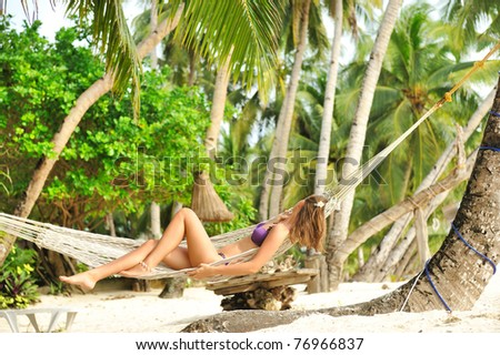 Woman in hammock on tropical beach - stock photo