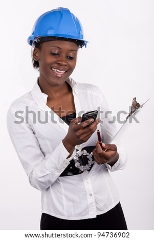 Woman in hard-hat with notepad sending a text message. - stock photo