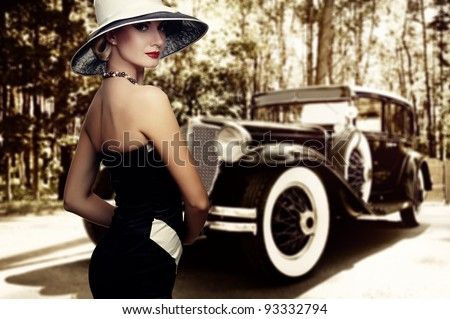 Woman in hat against retro car. - stock photo