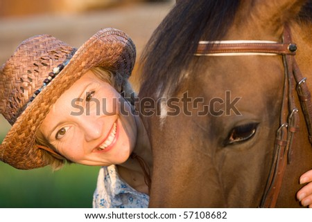 Woman in hat embrace brown horse. Close-up portrate - stock photo