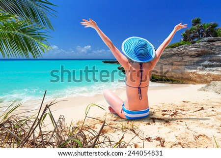 Woman in hat enjoying sun holidays on the beach of Mexico - stock photo