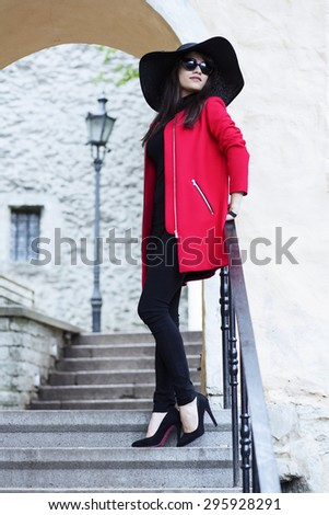 Woman in hat leaned on a fence - stock photo