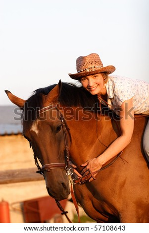 Woman in hat lying on brown horses neck - stock photo