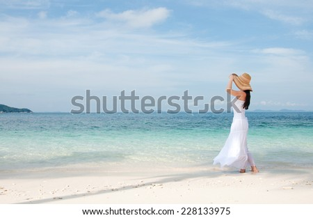 Woman in hat on shoreline at the tropical beach  - stock photo