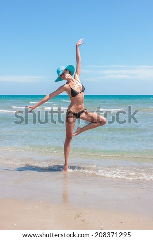 woman in hat on the beach in the summertime - stock photo