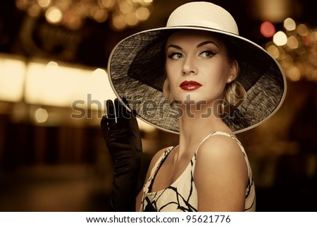 Woman in hat over blurred background.