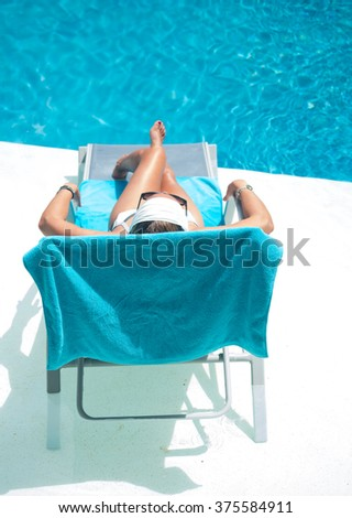 Woman in hat relaxation at private villa swimming pool sunbed - stock photo