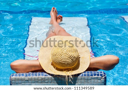 Woman in hat relaxation at swimming pool bed