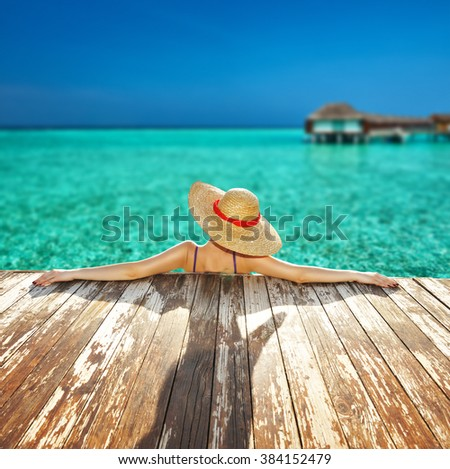 Woman in hat relaxing at beach jetty