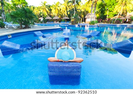 Woman in hat tanning on bed at swimming pool - stock photo