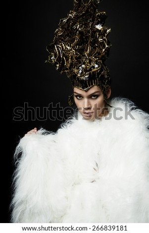 Woman in head wear and white fur coat