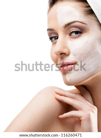 Woman in headband with lifting cream applied on a half of her face, isolated on white - stock photo