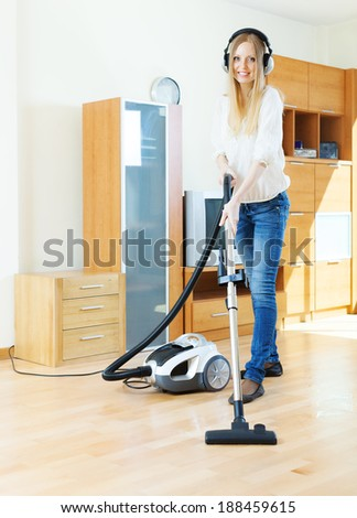 Woman in headphones cleaning with vacuum cleaner on parquet