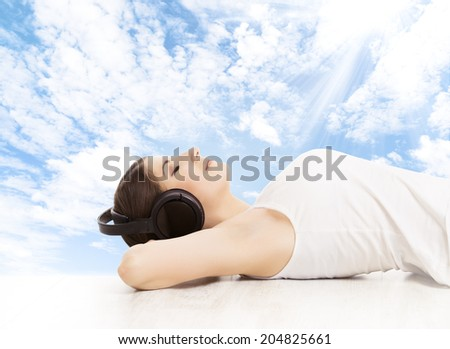 Woman in headphones dreaming listening to music. Girl relaxing over blue sky background  - stock photo