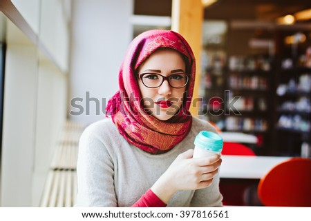 Woman in headscarf studying at the library with coffee - stock photo