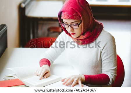 Woman in headscarf studying read a book - stock photo