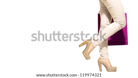 Woman in heels with shopping bag, isolated on white background